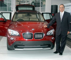 Adili Popat, chief executive officer of Bavaria Auto, next to the new 2010 BMW X1 series launched at the Nairobi showroom in Kenya yesterday