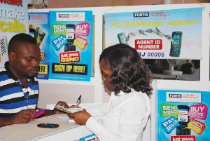 A Fortis Mobile Money subscriber depositing cash into her mobile wallet at an agent location in Wuse International Market, Abuja, Nigeria.