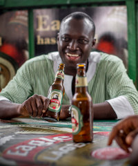 A consumer drinking Eagle, a beer brewed from cassava that was launched by SABMiller in Ghana. According to Trendwatching.com, 2014 will see more 'For Africa By Africa' products and services.