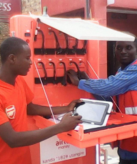 A franchisee of the M.S.K making use of the tablet provided to allow the sales of services electronically. Behind him is the M.S.K itself equipped with multiple ports to charge small electronics.