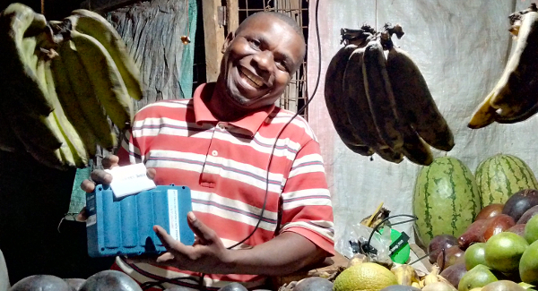 One of SunSweet Solar's customers with a solar kit. He owns a fruit shop in Kibaoni, 5km north-west of Ifakara.