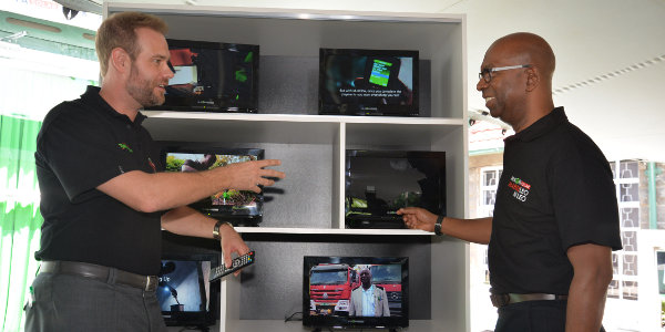 M-KOPA Solar CEO Jesse Moore explains the features of the M-KOPA solar powered digital flat screen TV to Safaricom CEO Bob Collymore. The solar powered TV that has been launched today will be accessible to both old and new M-KOPA customers.