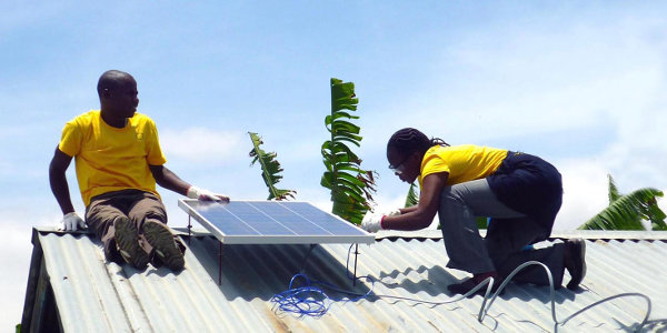 Mobisol employees installing a solar panel.