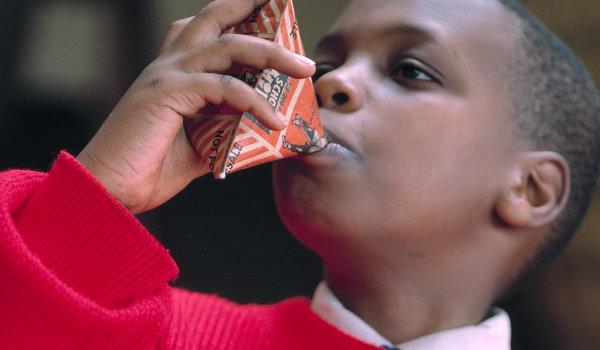 A boy drinking school milk in Kenya.