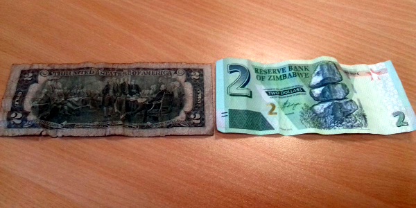 A well-used US$2 note next to the brand new $2 bond note. The bond note is now in circulation in Zimbabwe but economists and business people fear it will not hold its value to the strong US dollar.
