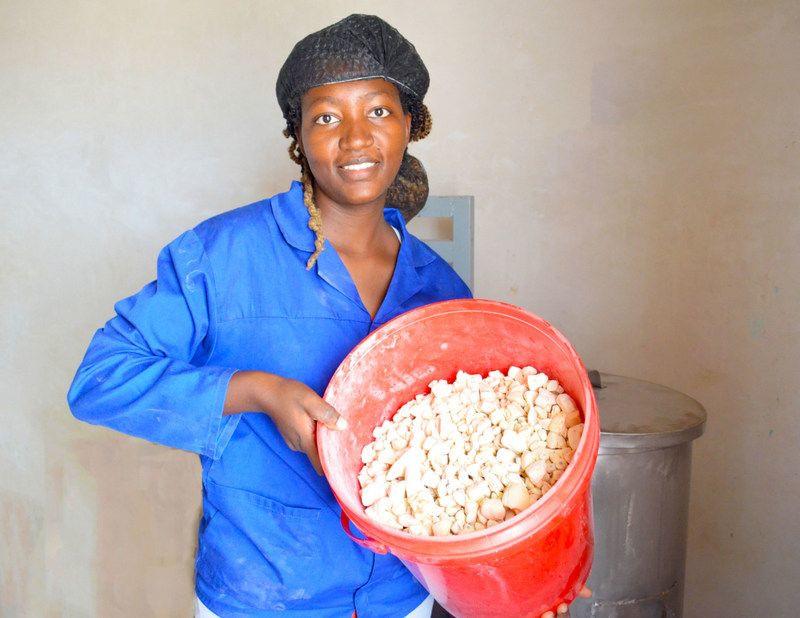 Kudzai Rosemary Makaza holding a bucket full of baobab.